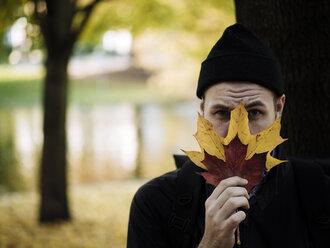 Portrait of man wearing woolly hat hiding behind autumn leaves - DASF000022