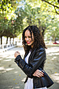 Portrait of smiling young woman with brown ringlets wearing black leather jacket - RAEF000623