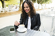 Portrait of happy young woman with cup of coffee at street cafe - RAEF000626