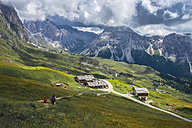 Italy, Dolomites, Odle mountain range, Hikers heading to a chalet - LOMF000081