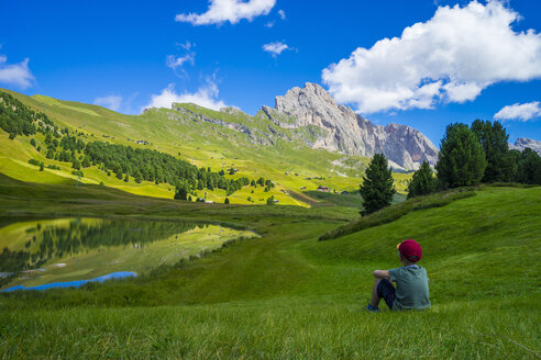 Italy, Dolomites, Odle range, Child resting in front of Seceda and lake Lech Sant - LOMF000090