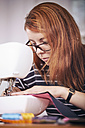 Portrait of young woman using sewing machine at home - SEGF000421