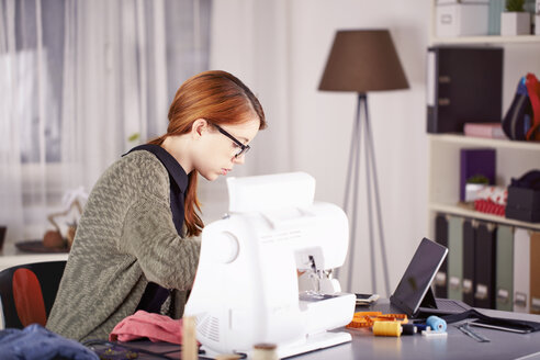 Portrait of young woman using sewing machine at home - SEGF000424