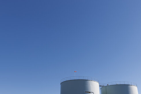 Netherlands, Roermond, two oil tanks in front of blue sky - VIF000441