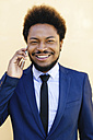 Portrait of smiling young businessman telephoning with smartphone - EBSF001009