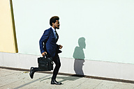 Young businessman with briefcase running on pavement - EBSF001012