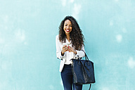 Portrait of smiling young businesswoman with smartphone and leather bag in front of a blue wall - EBSF001018