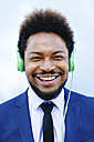 Portrait of smiling young businessman hearing music with headphones - EBSF001021