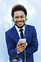 Portrait of smiling young businessman hearing music with headphones - EBSF001024