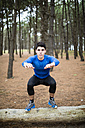 Athlete exercising box jumps in forest - RAEF000628