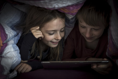 Brother and sister lying side by side using digital tablet under a blanket - SARF002301