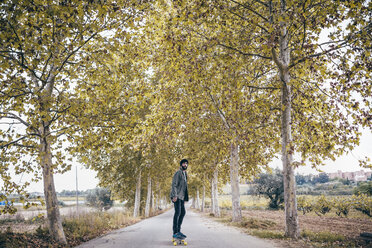 Spain, Tarragona, young man with longboard on autumnal country road - JRFF000174