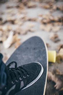 Man's black sneaker on longboard, close-up - JRFF000177