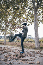Spain, Tarragona, young man playing with autumn leaves on country road - JRFF000180