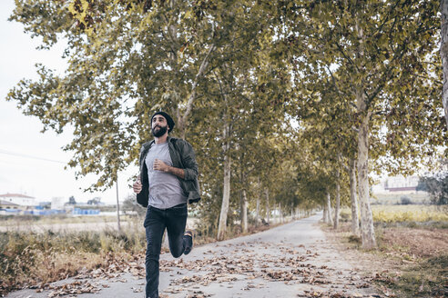 Spain, Tarragona, young man running on autumnal country road - JRFF000183
