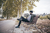 Spain, Tarragona, young man sitting on a bench at autumnal country road looking at his smartphone - JRFF000186