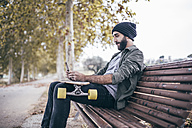 Spain, Tarragona, young man sitting on a bench with his longboard taking a selfie with smartphone - JRFF000189
