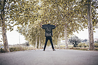 Spain, Tarragona, back view of young man with longboard on his shoulders on autumnal country road - JRFF000192