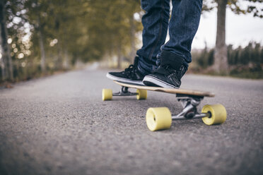Man standing on longboard on a country road, close-up - JRFF000195