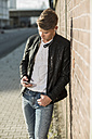 Young man wearing earbuds looking at cell phone - UUF005935