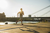 Young man running by the riverside - UUF005947