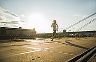 Teenage girl running by the riverside - UUF005950