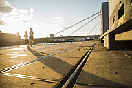Young couple running by the riverside - UUF005956