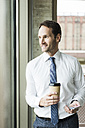 Portrait of smiling businessman with coffee and smartphone looking through window - UUF005969