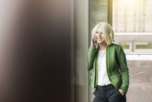 Portrait of smiling blond businesswoman telephoning with  smartphone - UUF005987