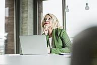Portrait of thinking businesswoman at her desk in the office - UUF006002