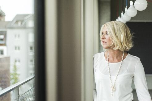 Portrait of pensive businesswoman  looking through window - UUF006008