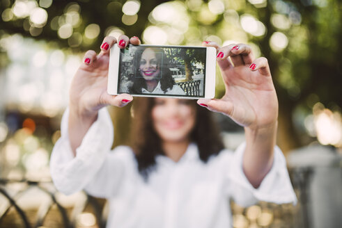 Young woman taking a selfie with her smartphone, close-up - RAEF000638