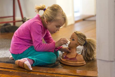Little girl applying make up on her doll - JFEF000747