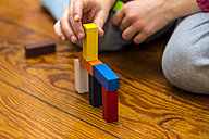 Little girl playing with building bricks on wooden floor, close-up - JFEF000750