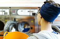 Back view of young woman in a launderette - MGOF001023