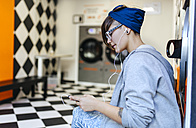 Young woman hearing music with earphones in a launderette - MGOF001029