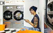 Tattooed young woman looking at her smartphone in a launderette - MGOF001035
