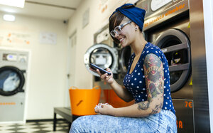 Portrait of tattooed young woman with smartphone in a launderette - MGOF001041