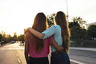 Back view of two female friends watching sunset arm in arm - GEMF000481