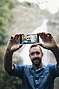 Bearded man taking a selfie with smartphone in front of a waterfall - RAEF000650