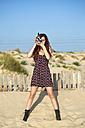 Spain, El Puerto de Santa Maria, young woman using old film camera on the beach - KIJF000027