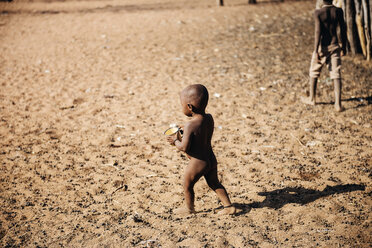 Namibia, Damaraland, back view of naked little boy with an empty cup in a Himba village - GEM000488