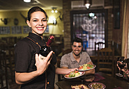 Portrait of smiling waitress serving wine and dishes - JASF000256