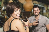 Smiling couple at bar drinking red wine - JASF000259