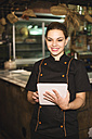 Smiling waitress in bar with digital tablet - JASF000262