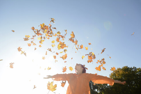Young woman throwing autum leaves in the air - BFRF001637