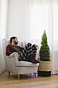 Man sleeping on armchair at home at Christmas time - EBSF001027