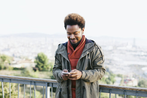 Spain, Barcelona, portrait of smiling young man looking at his smartphone - EBSF001045