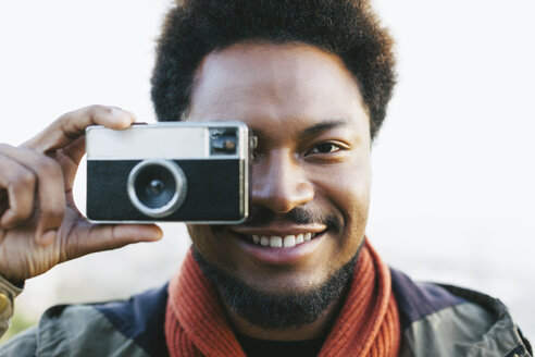 Portrait of smiling young man holding old camera - EBSF001048