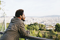 Spain, Barcelona, smiling young man leaning on railing looking at view - EBSF001051